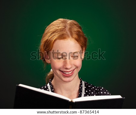 Portrait of a smart young girl enjoying a good book. - stock photo