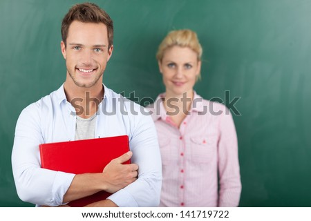 Portrait of a smart young man and woman with folder standing against green background - stock photo