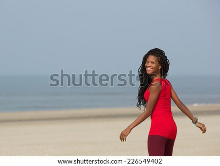 Portrait of a smiling african american woman walking at the beach   - stock photo