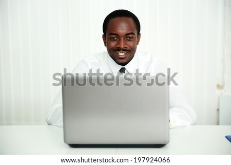 Portrait of a smiling african businessman sitting at the table with laptop in office
