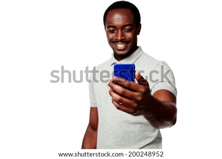 Portrait of a smiling african man using smartphone over white background - stock photo