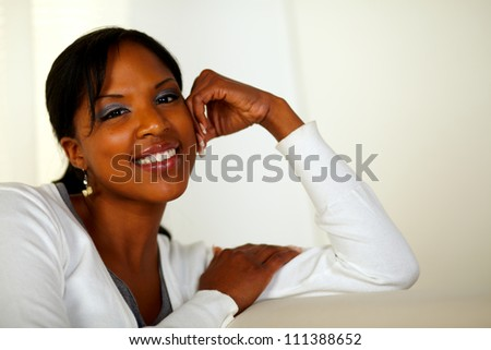 Portrait of a smiling afro-American young woman looking at you at home indoor