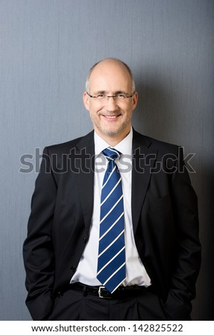 Portrait of a smiling and relaxed mature balding businessman, wearing a suit and a necktie, with hands in pockets, in front of a gray wall - stock photo