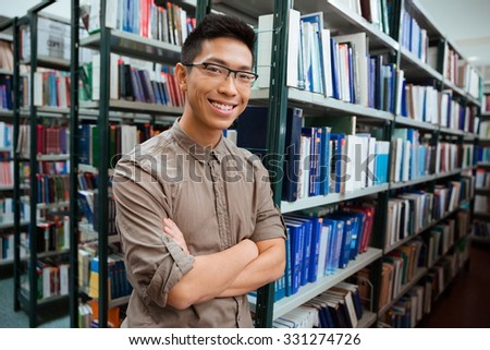 Portrait of a smiling asian man standing with arms folded in university library and looking at camera