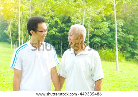 Portrait of a smiling asian senior man and his son