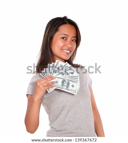 Portrait of a smiling asiatic young woman holding cash money while is looking at you against white background