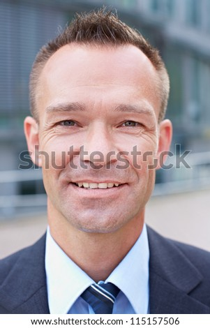 Portrait of a smiling attractive business man outside his office - stock photo