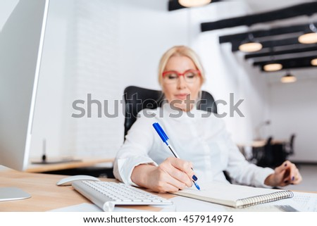 Portrait of a smiling attractive mature businesswoman writing in notebook in the office - stock photo