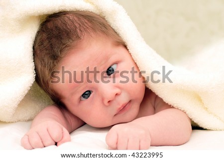 portrait of a smiling baby in a fabric - stock photo