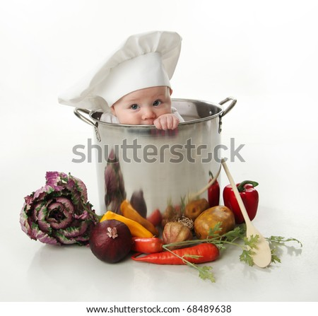 Portrait of a smiling baby sitting wearing a chef hat sitting inside a large cooking stock pot surrounded by vegetables and food, isolated on white - stock photo
