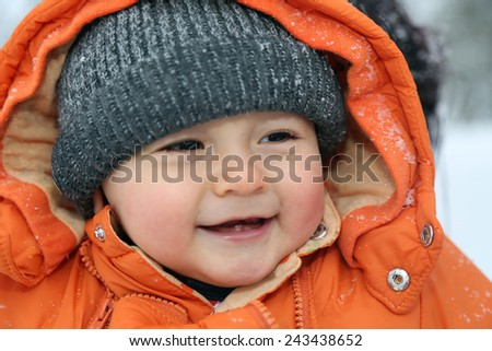 Portrait of a smiling baby with snow in winter with cap and winter clothes - stock photo