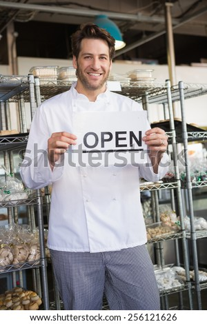 Portrait of a smiling baker holding open sign at the bakery - stock photo