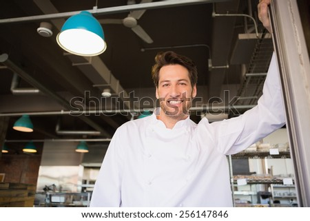 Portrait of a smiling baker standing at the bakery - stock photo