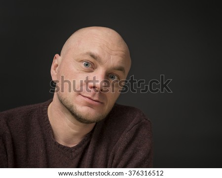 Portrait of a smiling bald man on a black background
