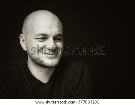 Portrait of a smiling bald man on a black background.  Black and white photo - stock photo