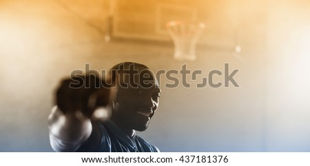Portrait of a smiling basketball player in a gymnasium - stock photo