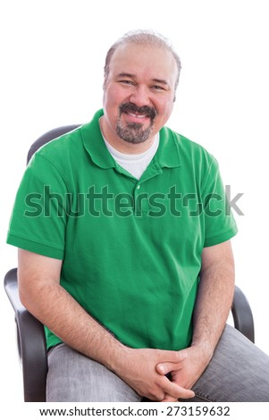 Portrait of a Smiling Bearded Middle Age Man, Wearing Plain Green Polo Shirt, Sitting on a Chair with Hands Crossed. Isolated on White Background.