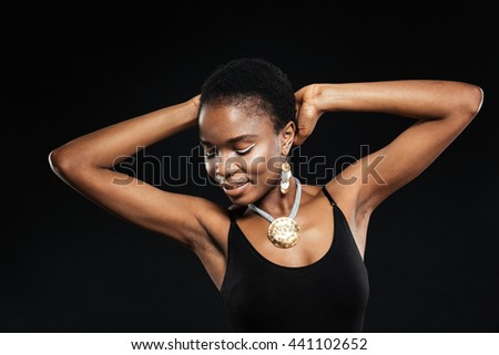 Portrait of a smiling beautiful african woman posing in studio isolated on the black background - stock photo