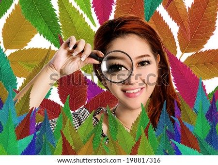 Portrait Of A Smiling Beautiful Asian Woman With A Magnifying Glass on Colored Leaves Background. - stock photo