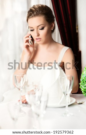 Portrait Of A Smiling Beautiful bride Talking On The Phone.  Portrait of young happy beautiful woman in restaurant.  - stock photo