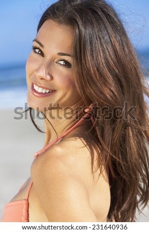 Portrait of a smiling beautiful brunette young woman or girl in bikini on a vacation beach