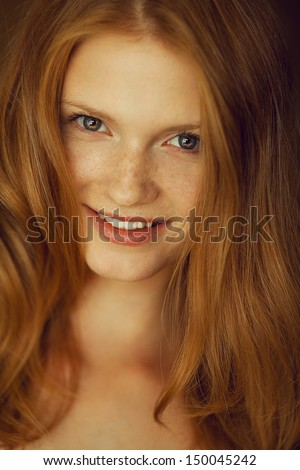 Portrait of a smiling beautiful red-haired (ginger) girl with funny freckles on her face posing over wooden background. Healthy long and wavy hair. Daylight. Close up. Studio shot