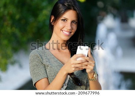 Portrait of a smiling beautiful woman texting with her phone in the garden. - stock photo