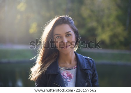 portrait of a smiling beautiful young girl in the park