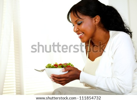 Portrait of a smiling beautiful young lady holding and looking to a green salad bowl on light background. With copyspace. - stock photo