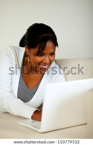 Portrait of a smiling black woman looking on laptop screen while lying on sofa