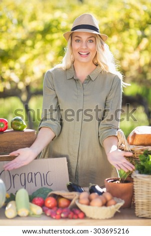Portrait of a smiling blonde presenting the table of local food - stock photo