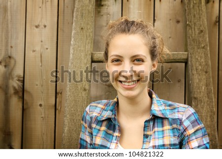 Portrait of a smiling blonde teenager against a wood fence