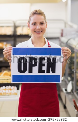 Portrait of a smiling blonde woman holding a sign in bakery - stock photo