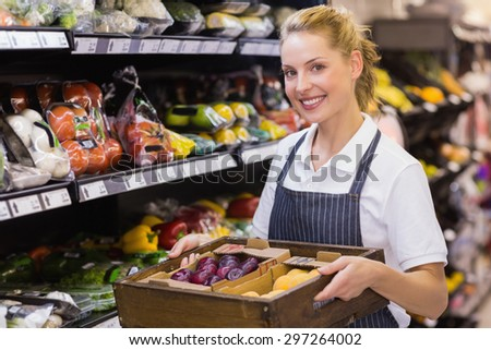 Portrait of a smiling blonde worker holding a box with vegetables in supermarker - stock photo