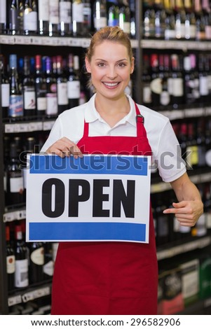 Portrait of a smiling bonde woman showing a sign in supermarket - stock photo