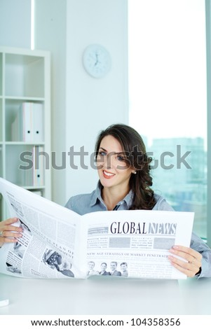 Portrait of a smiling business lady reading latest business news - stock photo