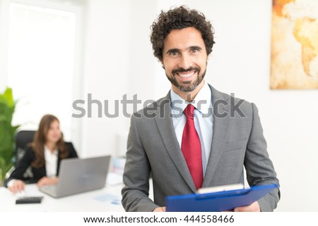 Portrait of a smiling business man in his office - stock photo