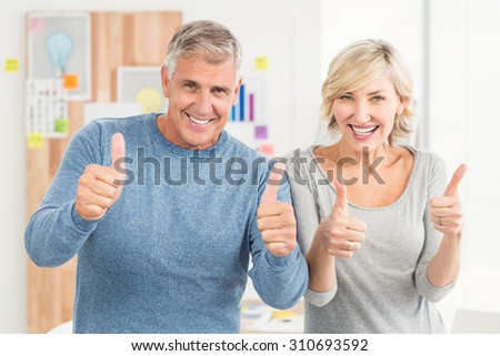 Portrait of a smiling business team gesturing thumbs up at office - stock photo