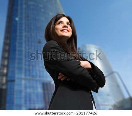 Portrait of a smiling business woman in front of a skyscraper - stock photo