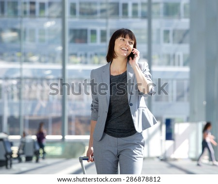 Portrait of a smiling business woman walking and talking with mobile phone at airport - stock photo