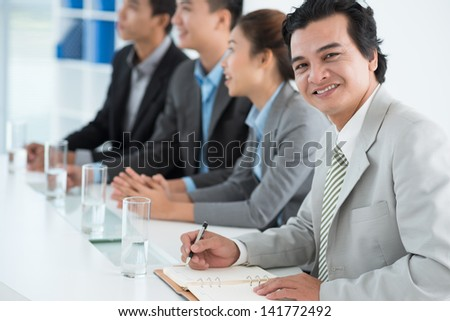 Portrait of a smiling businessman at the conference on the foreground