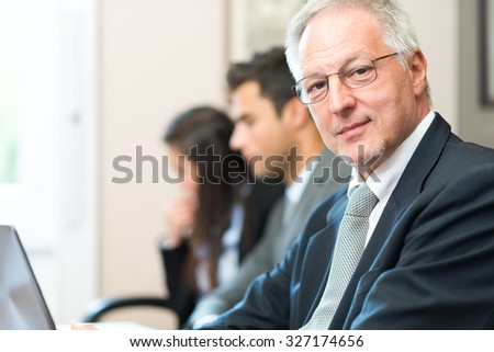 Portrait of a smiling businessman in front of his team - stock photo