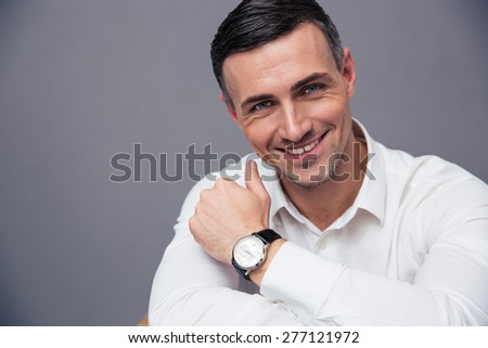 Portrait of a smiling businessman over gray background. Looking at camera - stock photo