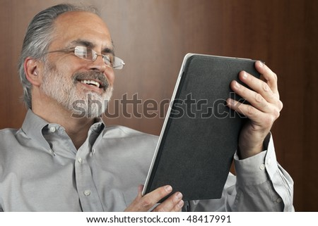 Portrait of a smiling businessman reading information from an electronic tablet. Horizontal shot.