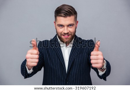 Portrait of a smiling businessman showing thumbs up over gray background - stock photo
