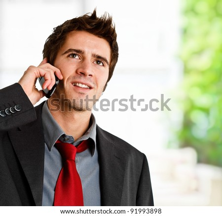 Portrait of a smiling businessman speaking on the phone - stock photo