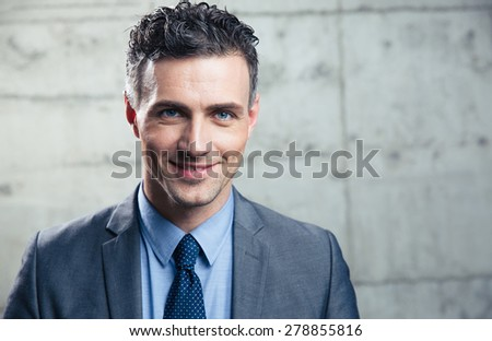 Portrait of a smiling businessman standing over concrete wall and looking at camera - stock photo