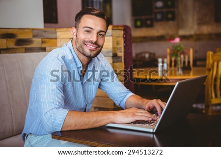 Portrait of a smiling businessman using his laptop at the cafe
