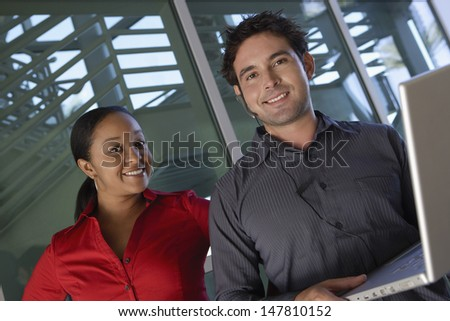 Portrait of a smiling businessman using laptop with female colleague - stock photo