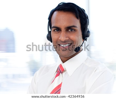Portrait of a smiling businessman with headsets on in a call centre - stock photo